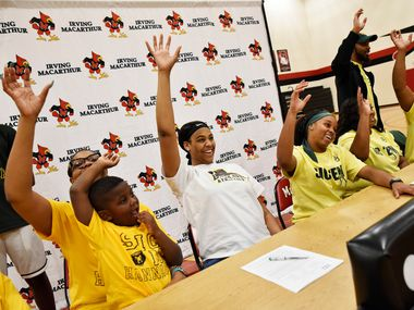 Irving MacArthur girls basketball players Hannah Gusters, center wearing white, and Sarah Andrews, at right, make the hand signal for the Baylor Bears after signing their letters of intent to play for Baylor University, Wednesday night Nov. 13, 2019 at Irving MacArthur High School in Irving. At left of Hannah is her mother Sheridane Gusters and brother Rylen Evans, 5. Right of Sarah is her parents Yolanda Ingram and Terry Woods, far-right.