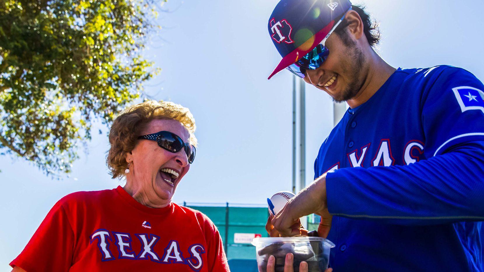 """Shirley Kost, conocida como la """"Dama de las Galletas"""", comparte un de sus creaciones horneadas con el pitcher de los Rangers de Texas, Yu Darvish, el 16 de febrero de 2017 en Surprise, Arizona."""