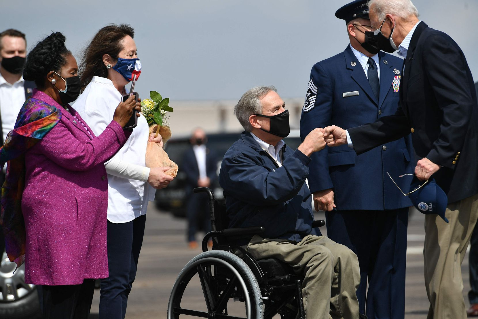 President Joe Biden greets Texas Gov.  Greg Abbott and his wife Cecilia Abbott (2nd L) at Ellington Field Joint Reserve Base in Houston on Feb. 26, 2021. At left is Rep. Sheila Jackson Lee. Biden visited Houston after severe winter storms left much of the state without electricity for days.