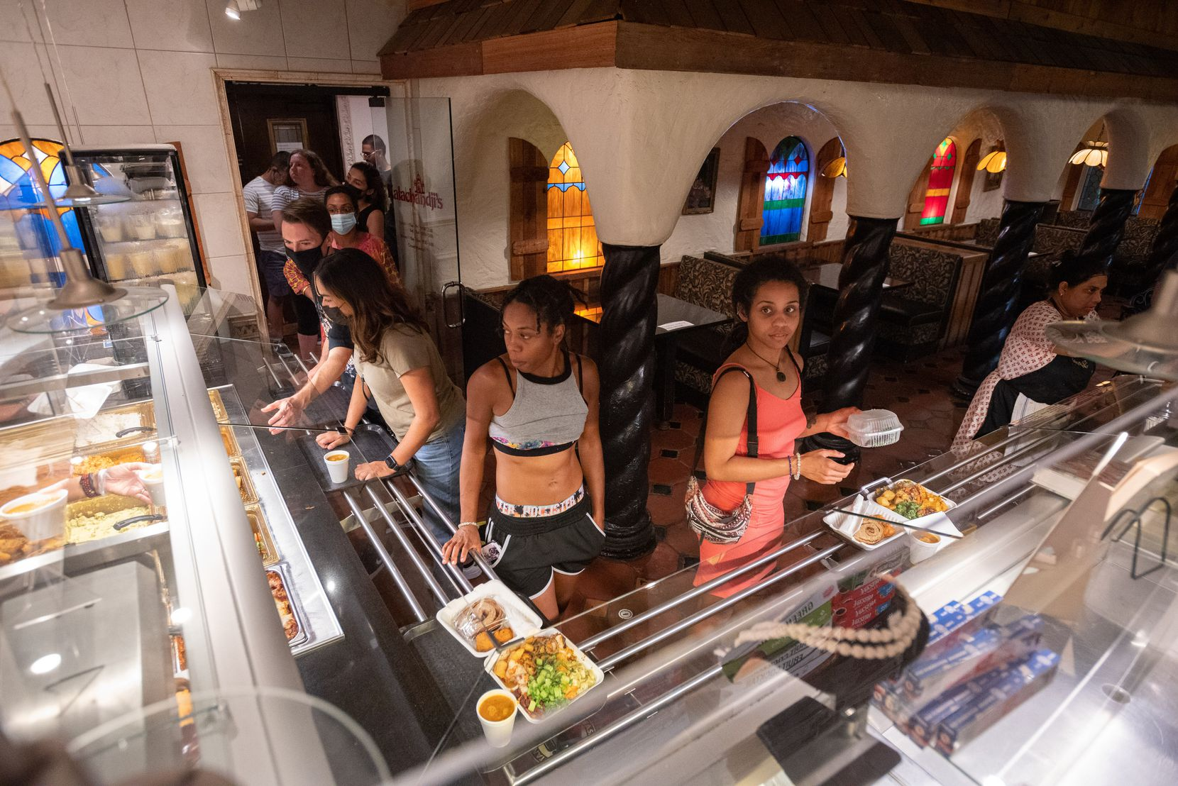 Shar Ma'at, left, and Jupiter-Morgan Dixon wait to pay for their meal in the buffet line at Kalachandji's vegetarian restaurant on Gurley Avenue in east Dallas, on Saturday, Aug. 28, 2021.