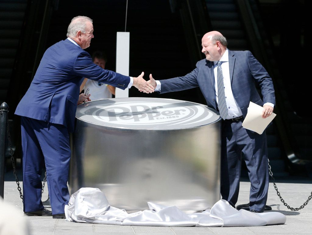 Dr Pepper's chief commercial officer Jim Trebilcock shakes hands with Dallas Cowboys executive vice president Stephen Jones after unveliing a Dr Pepper monument during the Ring of Honor Walk ceremony at The Star in Frisco on Monday, August 21, 2017.
