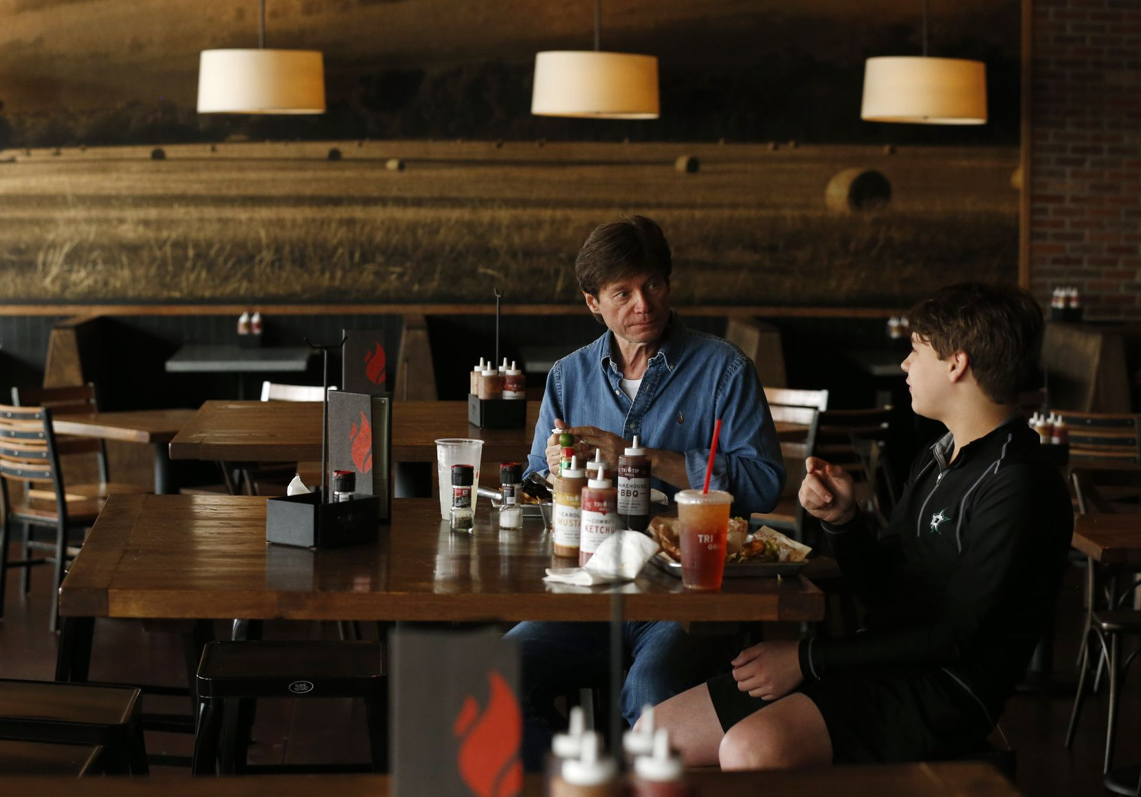 Roman Kikta and son Alex Kikta eat lunch together at Tri Tip Grill at The Star in Frisco, Texas, on Thursday, March 19, 2020. Texas Gov. Greg Abbott announced Thursday the temporary closing of schools, restaurants, gyms and bars statewide at a news conference.