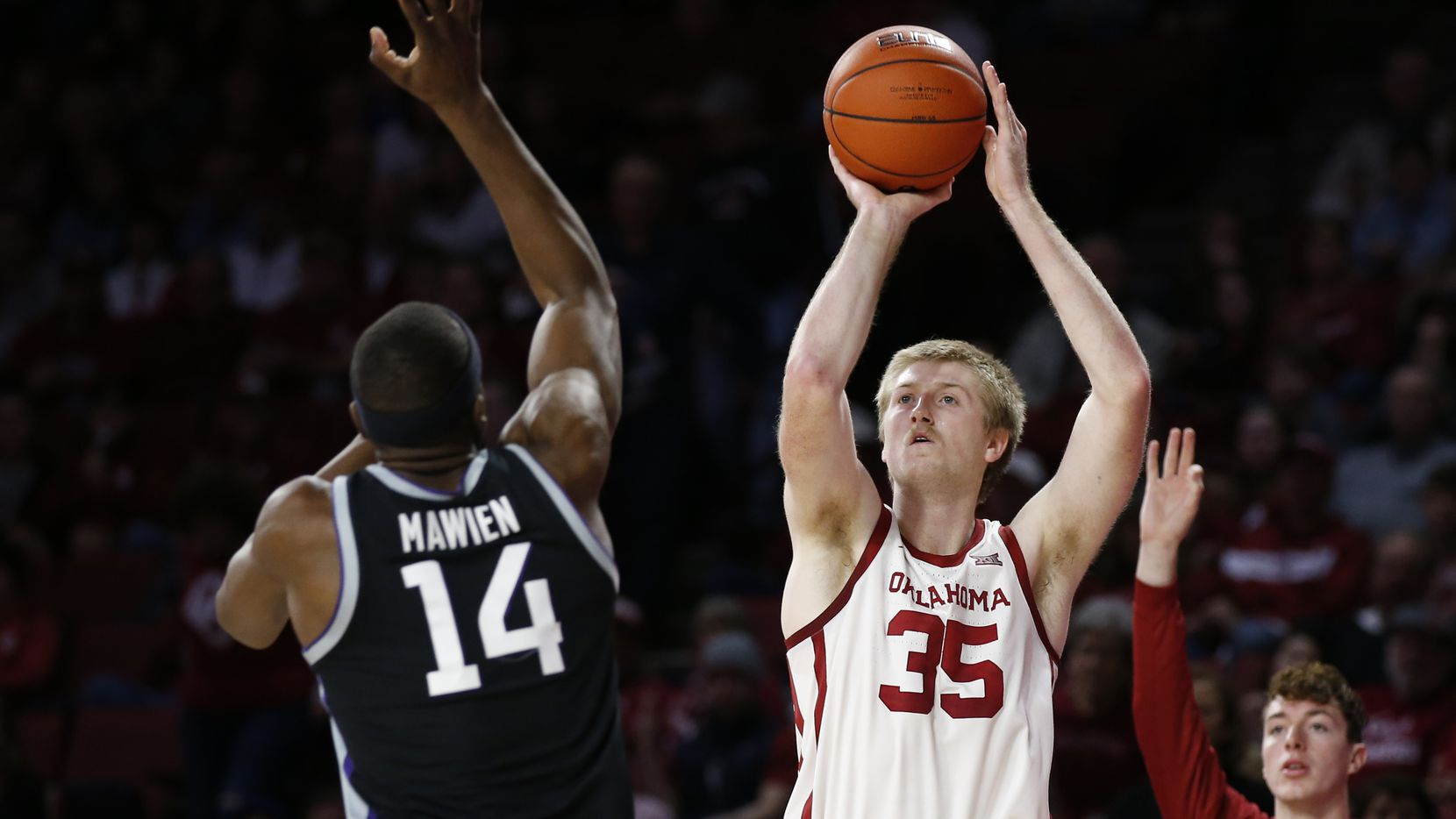 Oklahoma forward Brady Manek (35) shoots in front of Kansas State forward Makol Mawien (14) in the second half of an NCAA college basketball game in Norman, Okla., Saturday, Jan. 4, 2020.