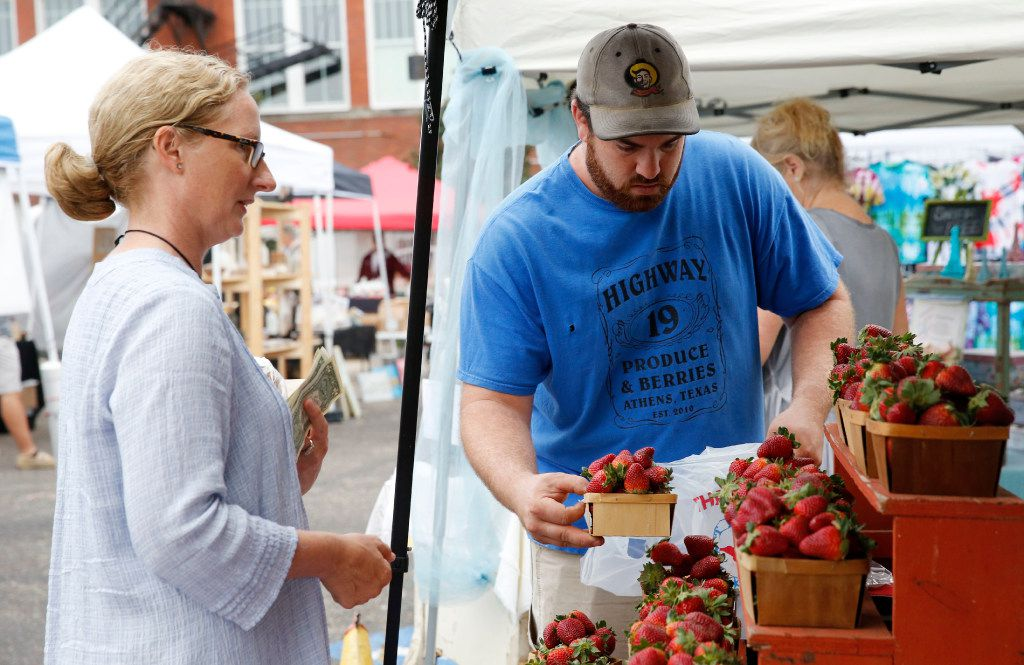 Bobby Bever bags some strawberries for Sarah Perry at the Highway 19 Produce & Berries booth during opening day for the Tyler Street Market run by Good Local in Dallas on Saturday, March 18, 2017. (Vernon Bryant/The Dallas Morning News)