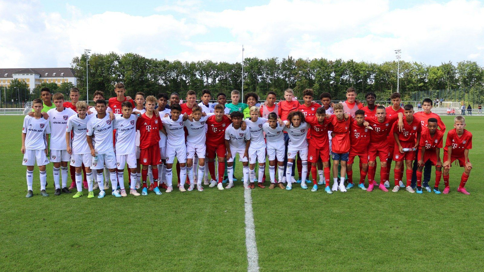 The FC Dallas U15s (in white) pose with the Bayern Munich U15s (in red) after their opening round game.