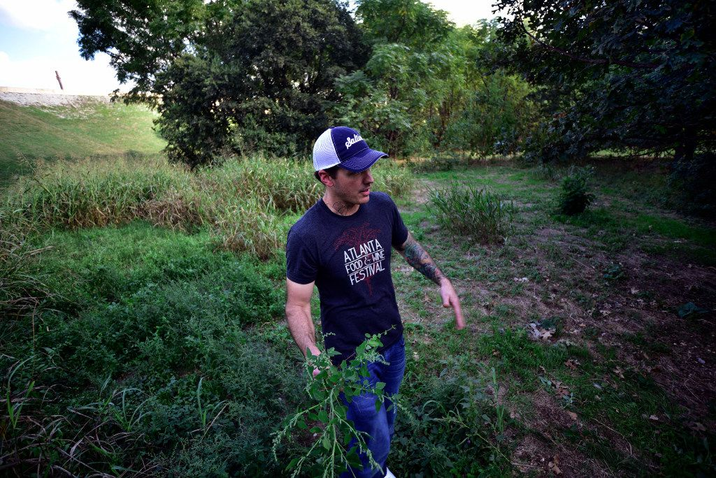 Chef Matt McCallister of FT33 restaurant holds a batch of wild spinach as he walks through an area near White Rock Lake looking for wild ingredients.