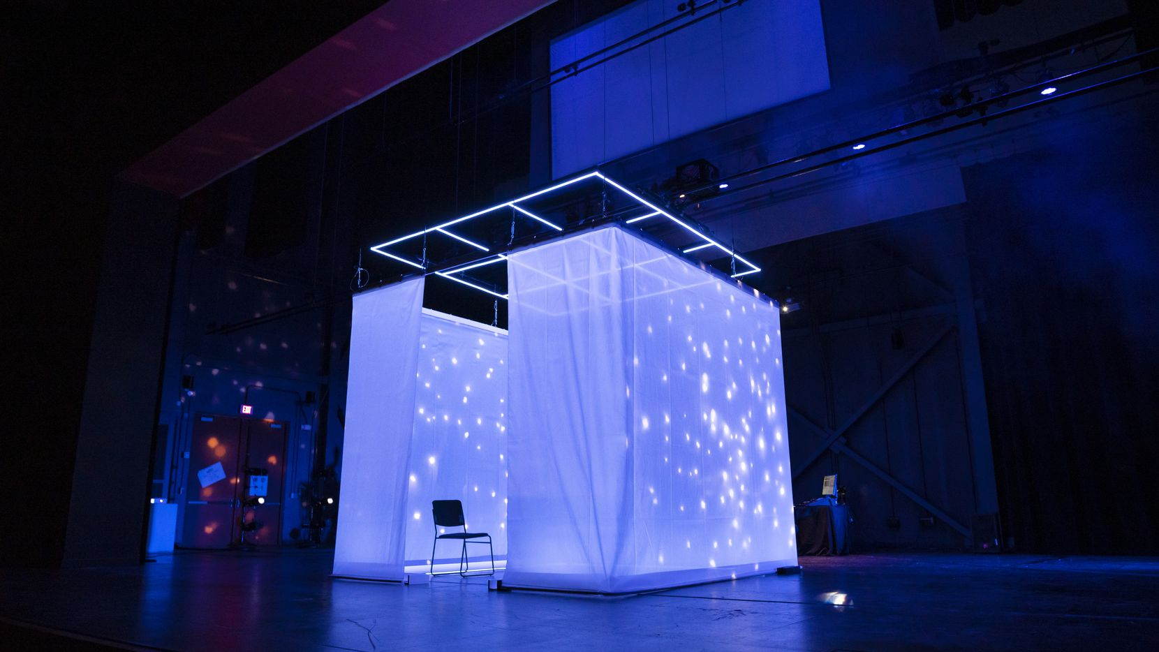 """A curtained-off square serves as projection screen and audience pod in """"The Cube"""" at the Latino Cultural Center."""