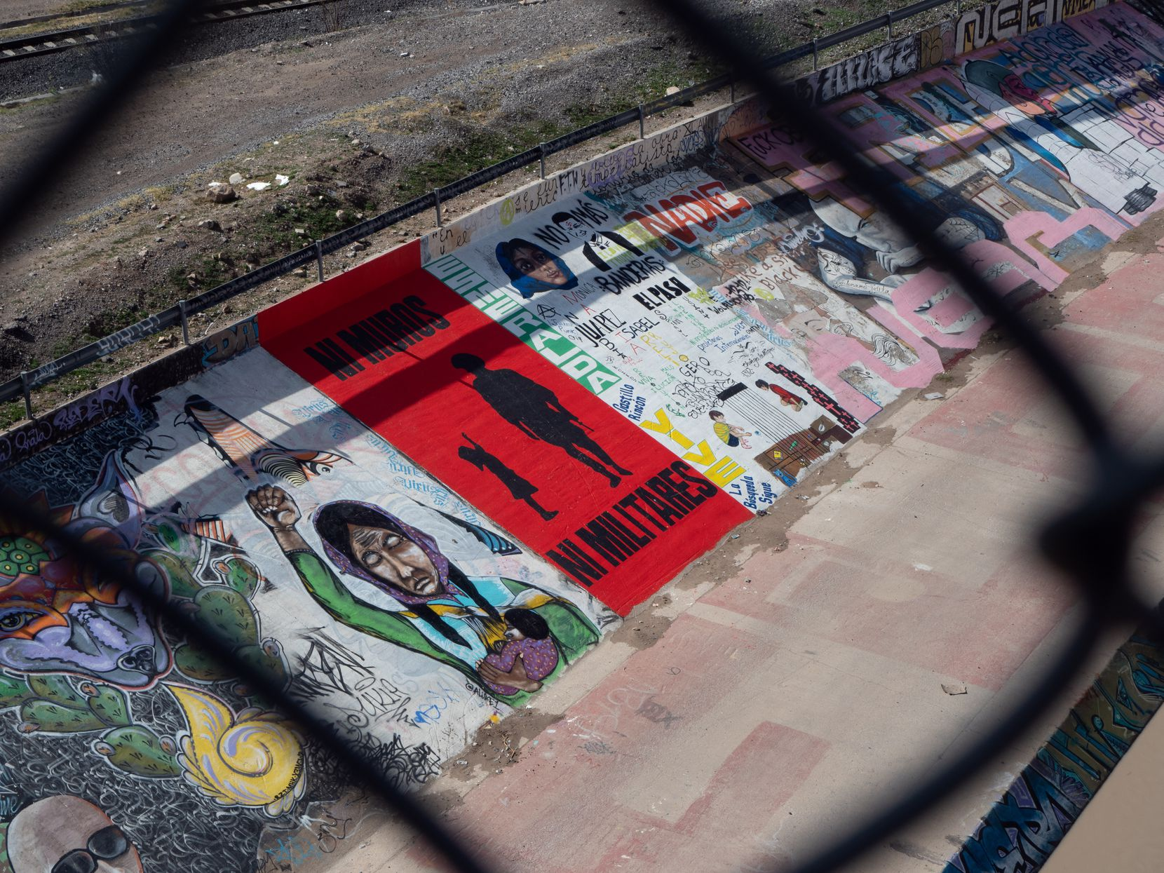 "A fresh mural the Mexican side of the Rio Grande in Juarez reads, in red and black letters,  ""NO WALLS NO MILITARY."""