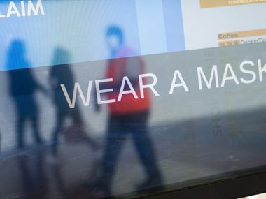 The arrivals board displays a message about wearing masks at Ronald Reagan Washington National Airport, May 5, 2020 in Arlington, Virginia. Most major airlines are now requiring passengers to wear face coverings to help prevent the spread of the coronavirus.