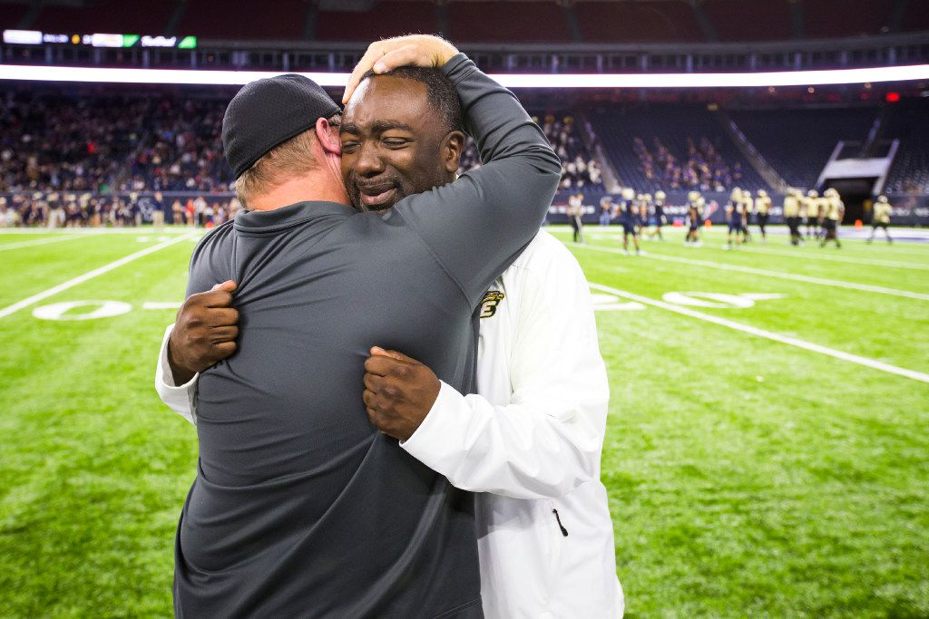 DeSoto assistant coach Brandon Harrison (right) hugs head coach Todd Peterman (back to camera) in the final moments of a victory over Klein Collins in a UIL Class 6A Division II state semifinal playoff football game at NRG Stadium on Saturday, Dec. 10, 2016, in Houston. Harrison was awarded the game ball after the win.  His father passed away earlier that week. (Smiley N. Pool/The Dallas Morning News)