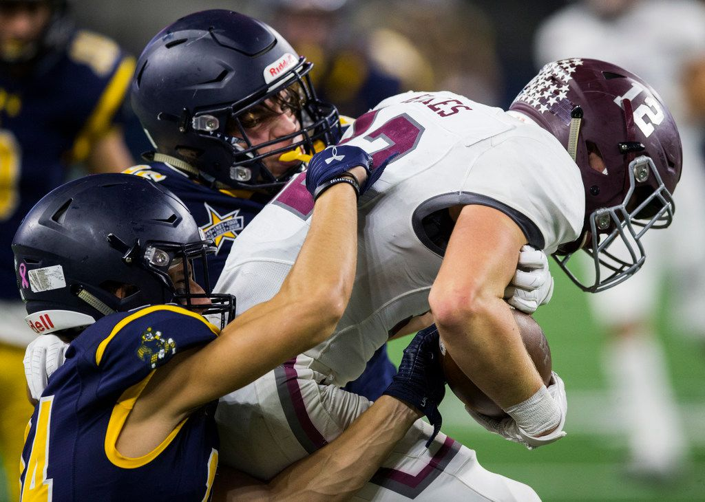Highland Park defensive back Christian Wright (14) and Sam Morse (96) tackle Magnolia defensive back Nathan Hakes (12) on a punt return during the second quarter  of a Class 5A Division I area-round playoff game between Magnolia and Highland Park on Thursday, November 21, 2019 at AT&T Stadium in Arlington. (Ashley Landis/The Dallas Morning News)