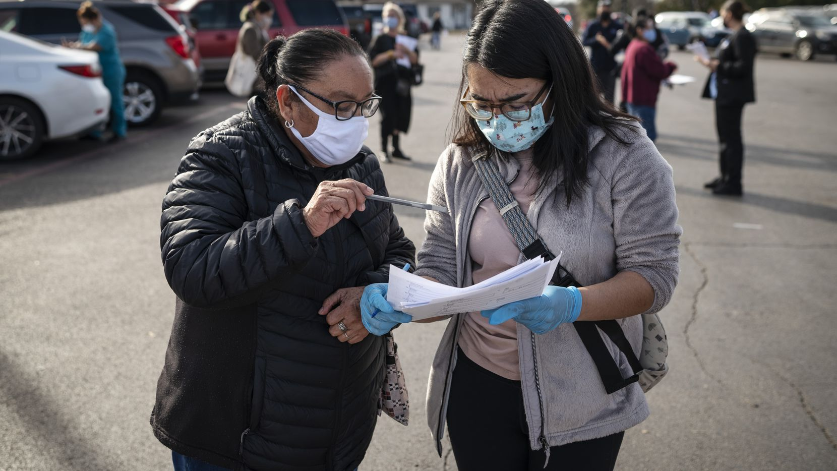 Maria Hernandez, 68, works with registered nurse Ruth Olvera, right, as she helps to register Hernandez for a COVID-19 vaccine during a registration event hosted by Dallas County Health and Human Services outside of a Supermercado Monterrey grocery store in Oak Cliff, on Tuesday, Feb. 02, 2021 in Dallas.