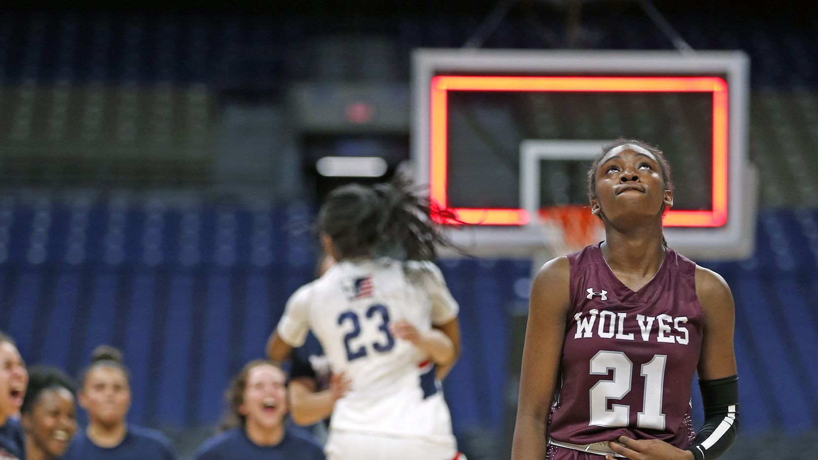 Mansfield Timberview Forward Stephanie Mosley #21 looks up as SA Veterans celebrates in background in a 5A semifinal on Thursday, March 5, 2020 at the Alamodome. San Antonio Veterans defeated Mansfield Timberview 45-44.