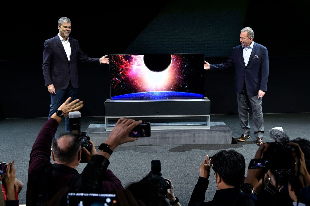 LG Electronics USA Senior Director of Home Entertainment Product Marketing Tim Alessi (left) and LG Electronics USA Senior Vice President of Marketing David VanderWaal unveil a LG Signature OLED TV R during a LG press event for CES 2019 at the Mandalay Bay Convention Center on January 7, 2019 in Las Vegas, Nevada.