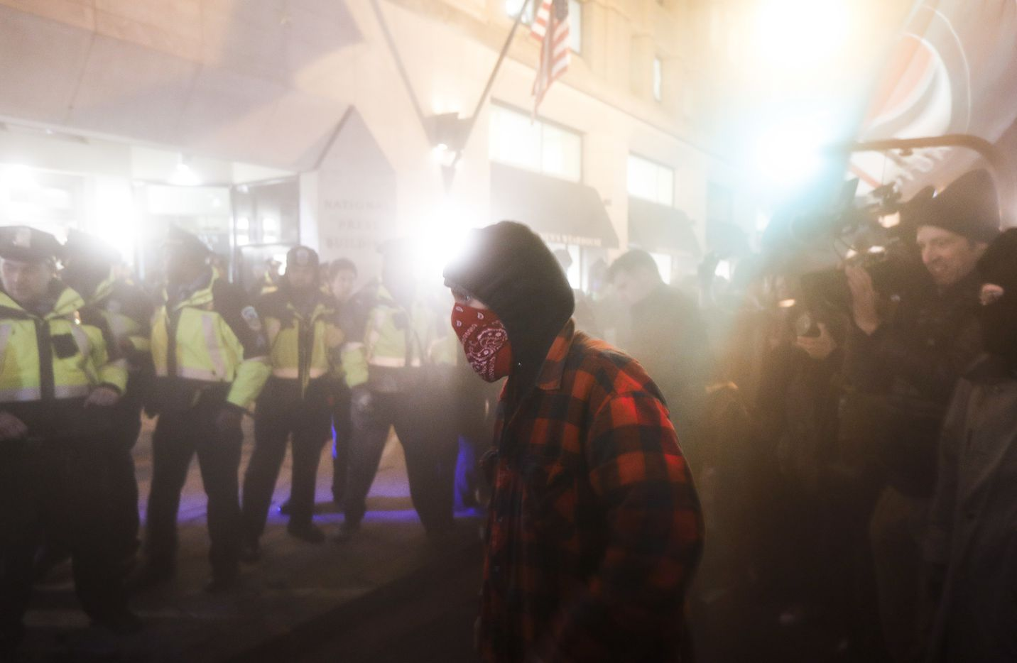 A protester walks through a cloud of gas sprayed by police following outside the National Press Club Thursday, Jan. 19, 2017, in Washington.