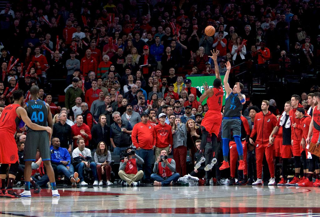 Dallas Mavericks forward Luka Doncic, right, makes a 3-point basket over Portland Trail Blazers forward Maurice Harkless with 0.6 seconds left to force overtime during the second half of an NBA basketball game in Portland, Ore., Sunday, Dec. 23, 2018. (AP Photo/Craig Mitchelldyer)