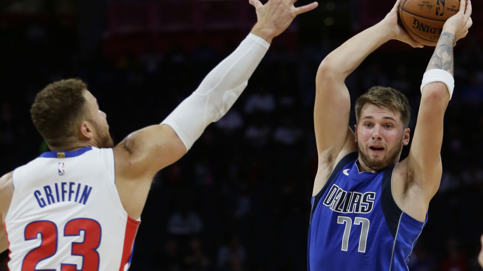 Dallas Mavericks forward Luka Doncic (77) passes the ball as Detroit Pistons forward Blake Griffin (23) defends during the second half of an NBA preseason basketball game Wednesday, Oct. 9, 2019, in Detroit.