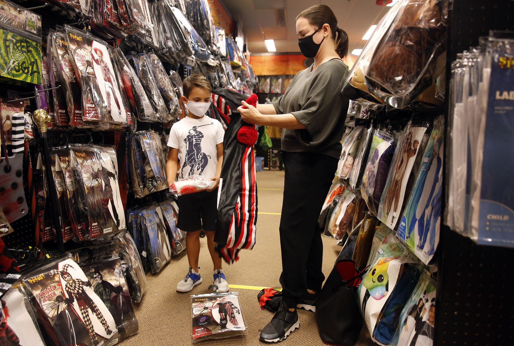 Carey Marin of Richardson checks to see whether a twisted circus clown outfit will fit her son, Joshua, at Spirit Halloween, a pop-up store on Coit Road in Dallas.