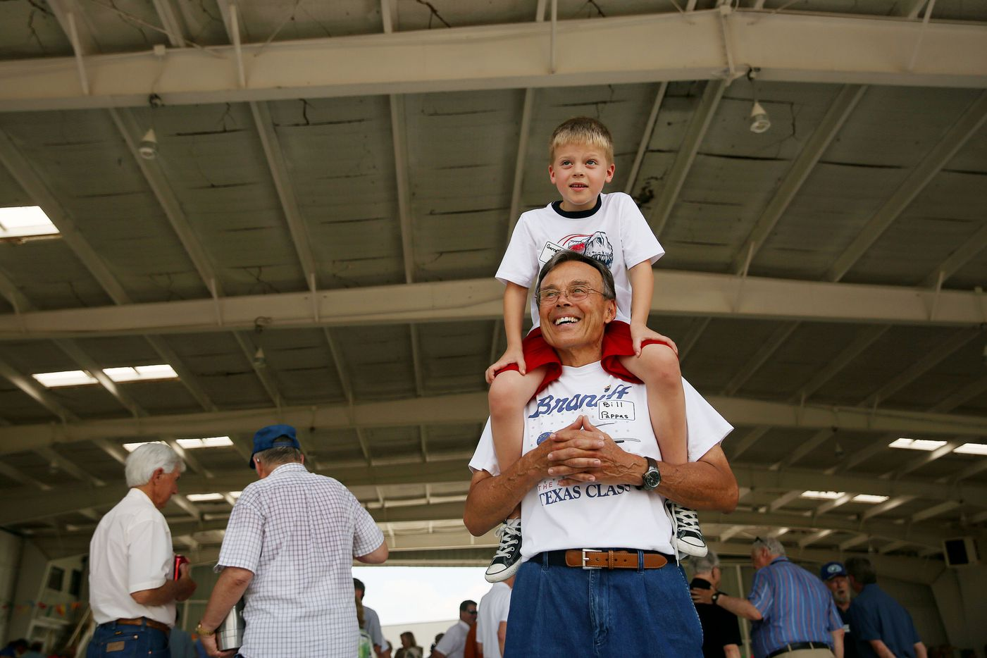 Bill Pappas, who was a pilot for Braniff for nine years, carries his grandson Garrett Pappas, 6, as they look at the runway during the 41st annual Braniff International Airways pilots picnic at Denton Municipal Airport.