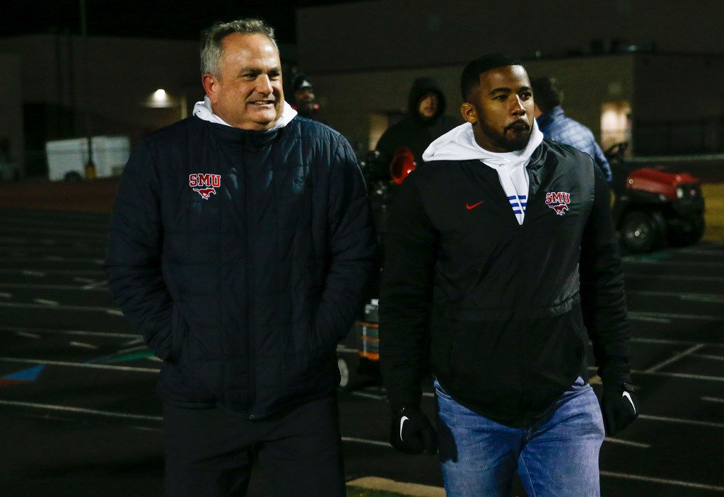 Southern Methodist head football coach Sonny Dykes, left, and assistant receivers coach RaÕShaad Samples arrives via helicopter to a high school football match up between Cedar Hill and DeSoto on Thursday, Nov. 7, 2019. (Ryan Michalesko/The Dallas Morning News)
