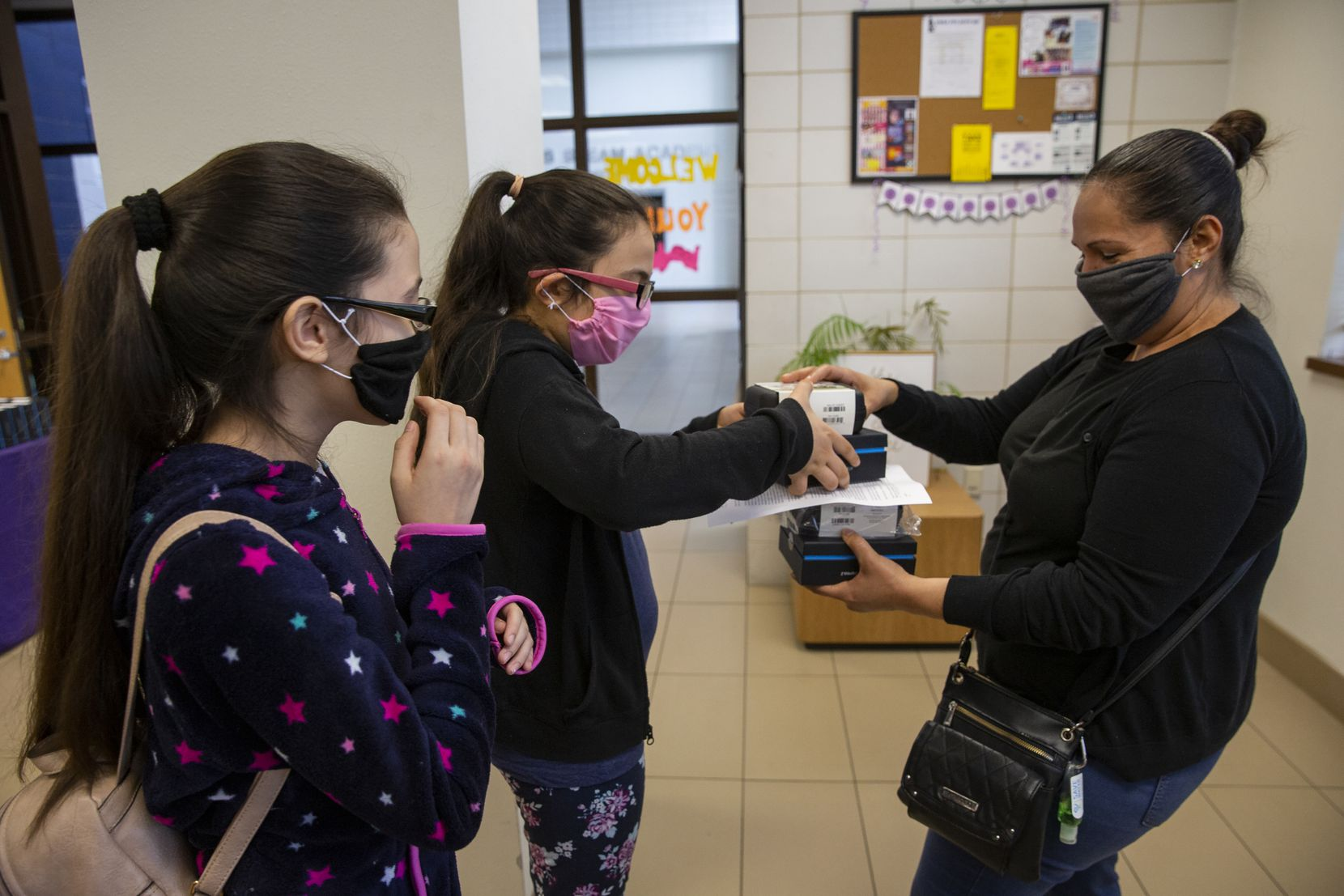 Adlemi Morales (left), 13, and Emeline Morales, 11, grab Wi-Fi hotspots provided by DISD from their mom Imelda Tinajero at Young Women's STEAM Academy at Balch Springs in Dallas. The girls were using their neighbors' Wi-Fi to complete homework.