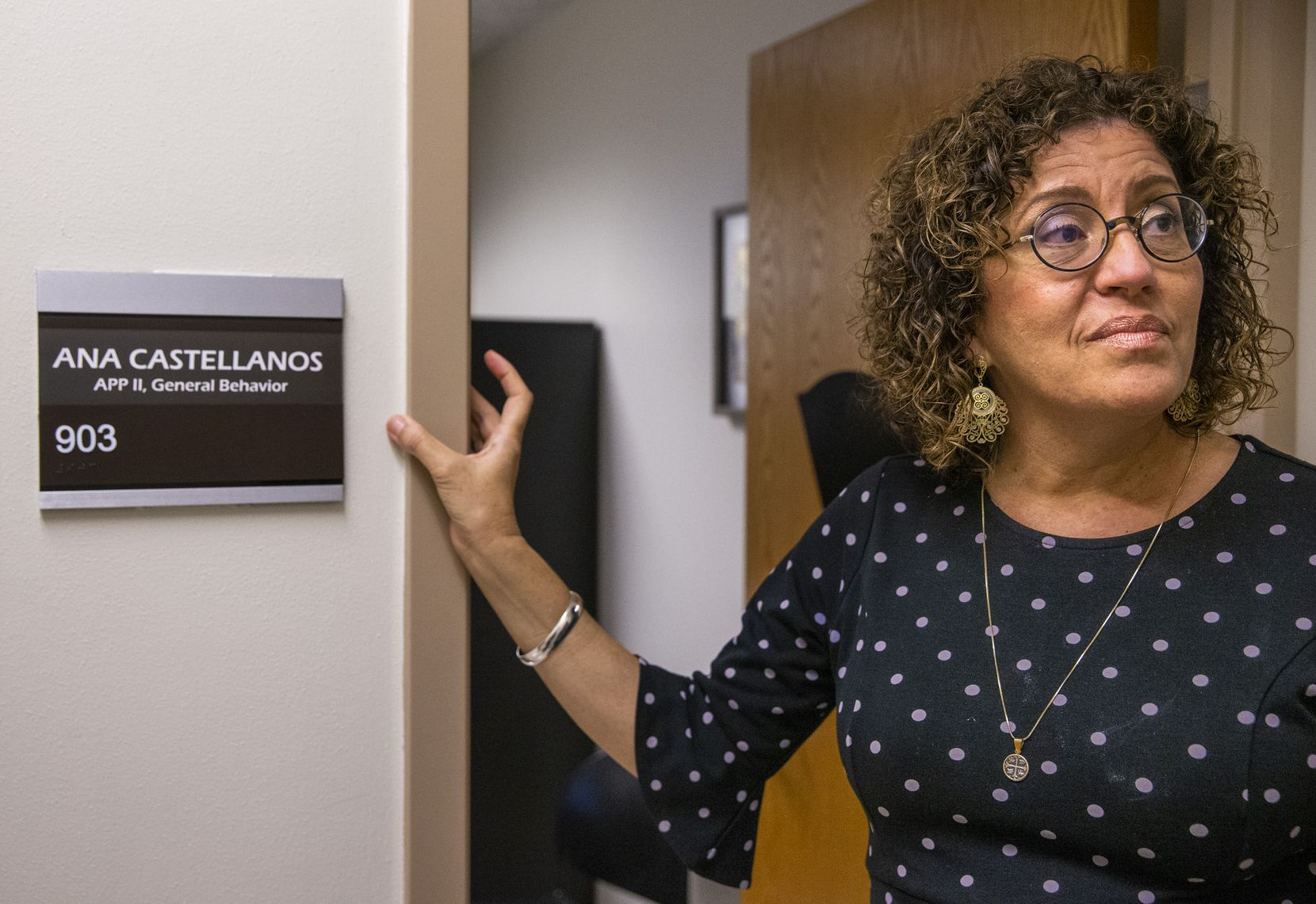 Ana Castellanos, a behavioral health provider, speaks to a visitor outside her office at the mental health hub of the deHaro-Saldivar Health Center in Dallas.
