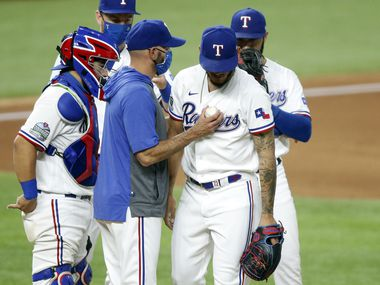Texas Rangers manager Chris Woodward taps relief pitcher Jonathan Hernandez (72) on the chest as he's pulled from the Oakland Athletics game in the eighth inning at Globe Life Field in Arlington, Texas, Wednesday, August 26, 2020.