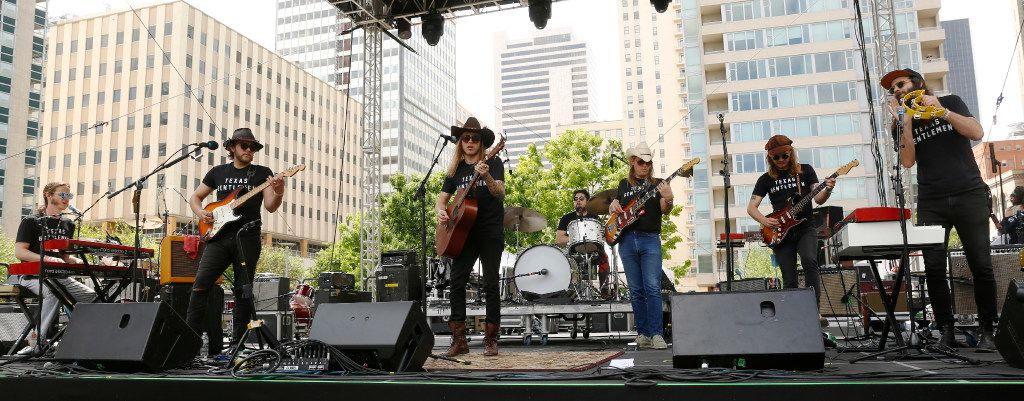 The Texas Gentleman perform against the Dallas skyline at the Old 97's Country Fair held at Main Street Garden in downtown Dallas Saturday April 8, 2017. (Ron Baselice/The Dallas Morning News)