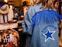 Game Day Style founder Brittany Cobb models a jacket for a photo at her shop located across from the Star in Frisco.