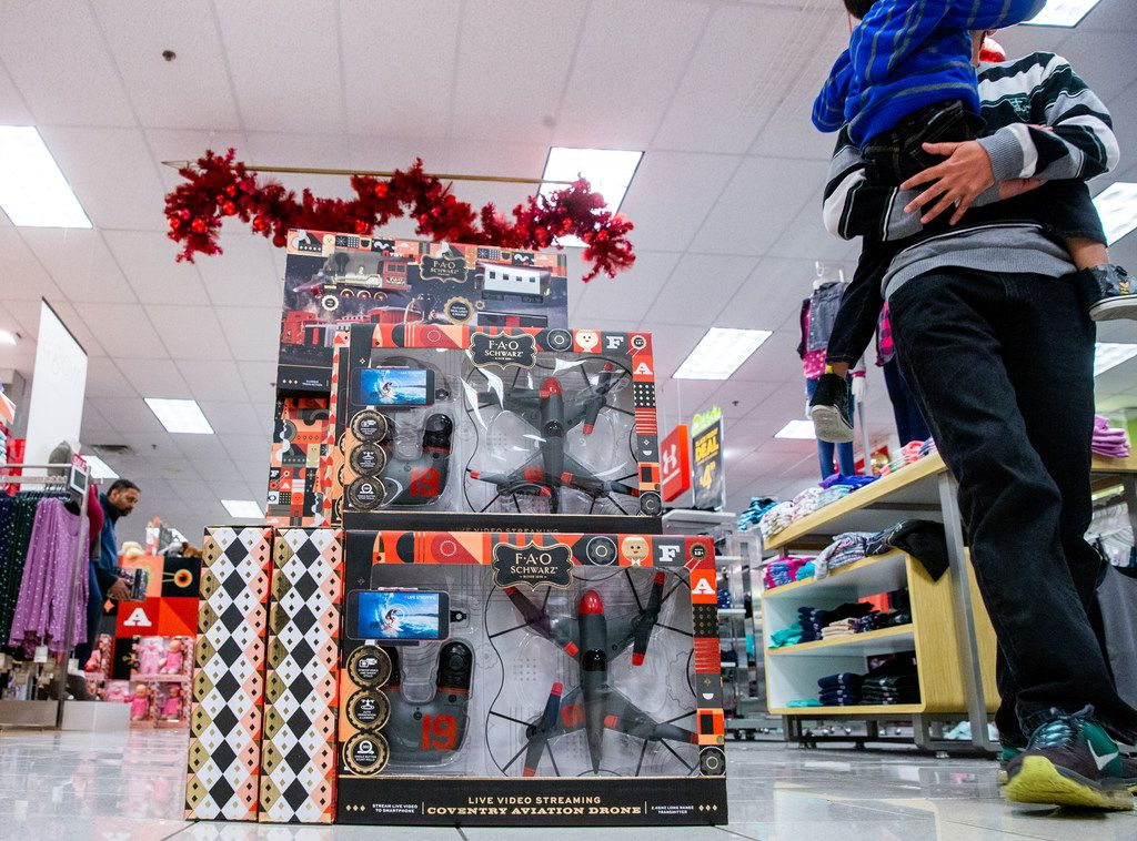 A customer holds a young child while walking past a toy drone during Black Friday shopping at Kohl's in Plano.