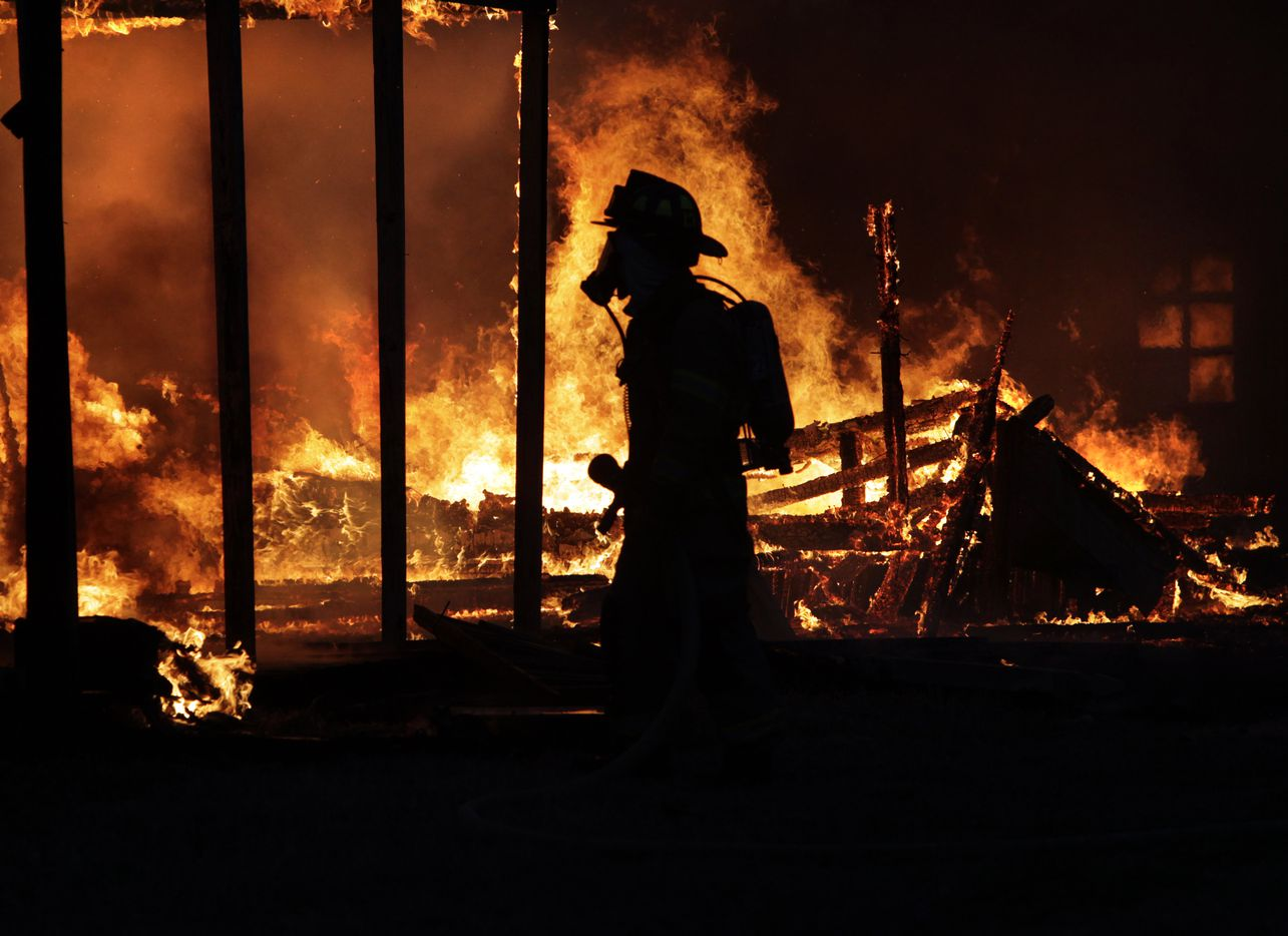 Intense flames silhouetted a Ferris firefighter before sunrise as he waited for water at Old Fort Dallas, a theme park at 300 Patrick Pike Road between Wilmer and Ferris, on March 21, 2011. The location had been closed for more than 10 years but had often been used as sets for movies and television shows. It was the second time in less than five months that sections of the park had burned.