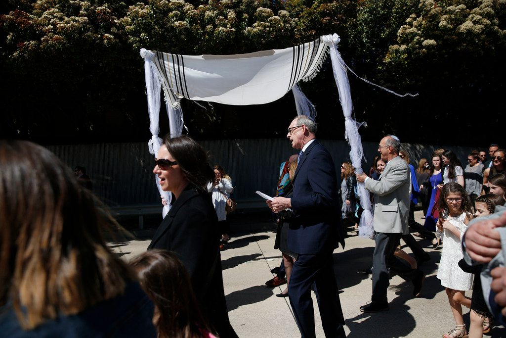 Rabbi Stefan Weinberg sings during a procession carrying a torah made in honor of his late wife, Wende Weinberg, from their Plano home to nearby Anshai Torah, the synagogue they founded together.
