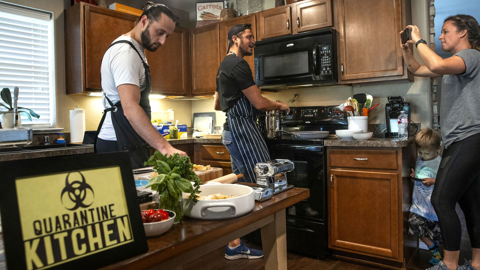 Benchmark Hospitality conference planner Christie Wilson (right) films chef Kyle Wilson (center) and sous-chef Kreshnik Mucllari as they prepare various pasta shapes to broadcast to other company employees on Facebook Live from Wilson's home in Fort Worth in September.