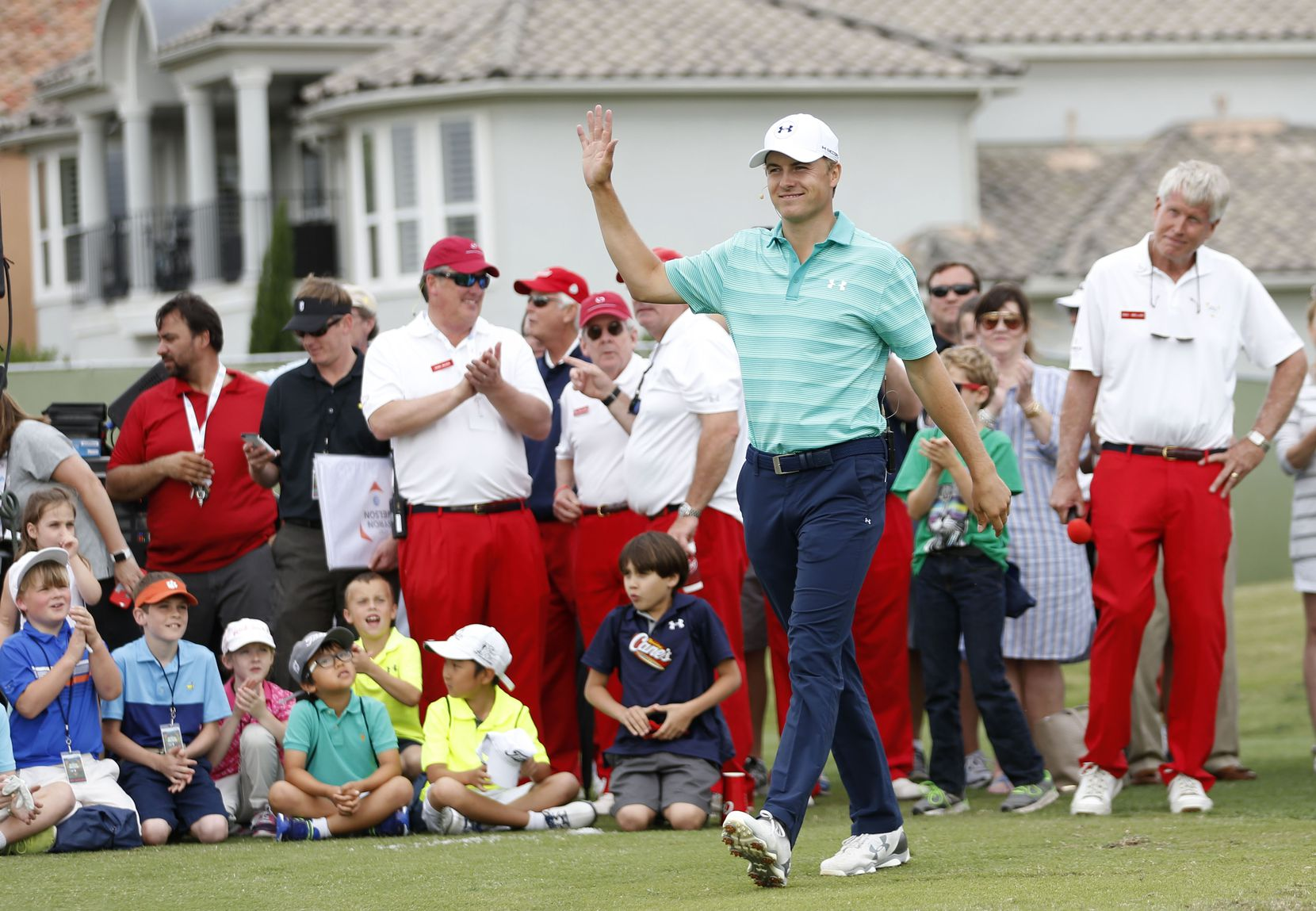 Jordan Spieth waves to the crowd as he is introduced  during a youth golf clinic at TPC Four Seasons in Irving before last year's Byron Nelson tournament. Behind him are members of the Dallas Salesmanship Club, wearing their trademark red pants.