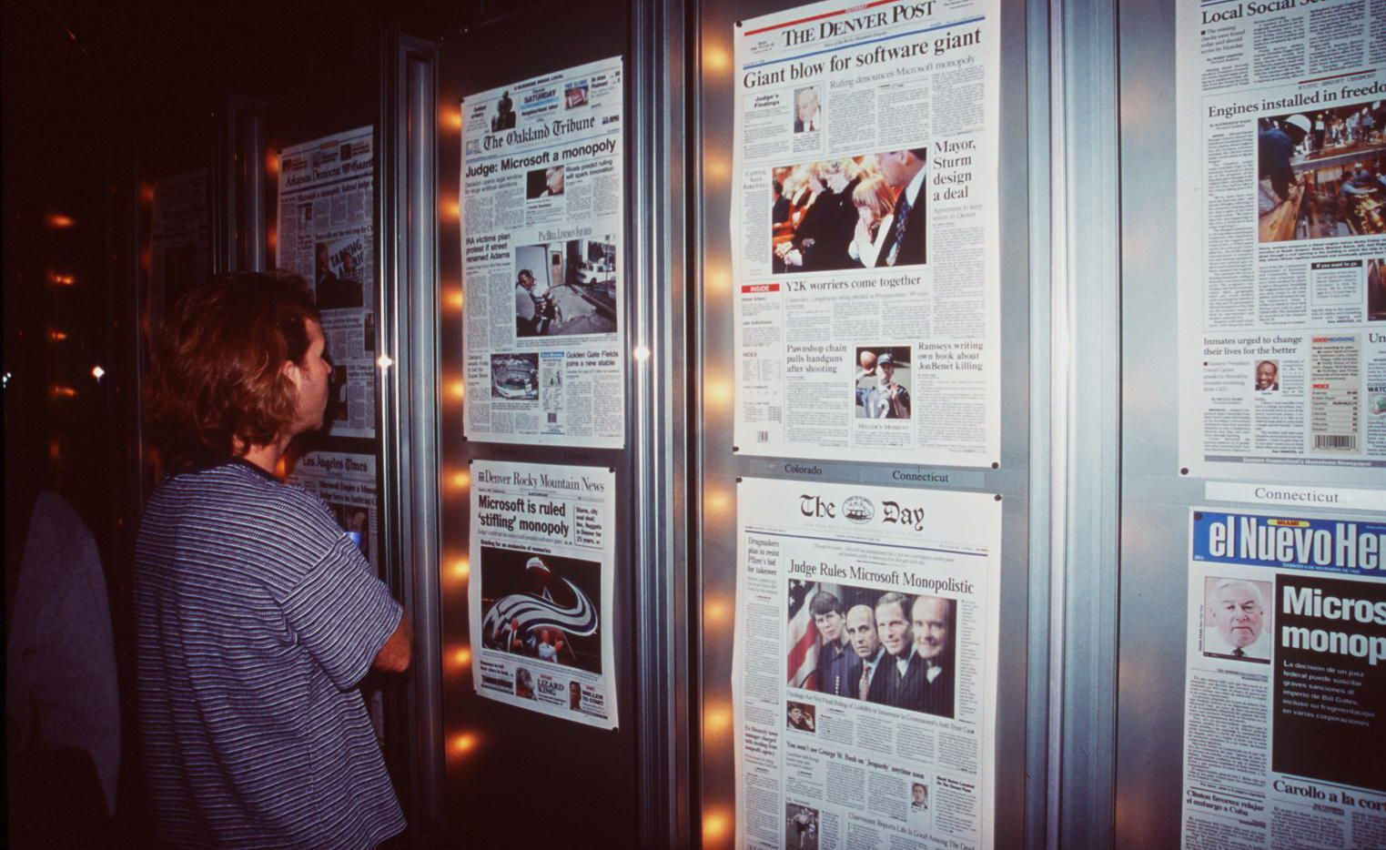 Visitors to the Newseum read front pages of newspapers digitally delivered daily.