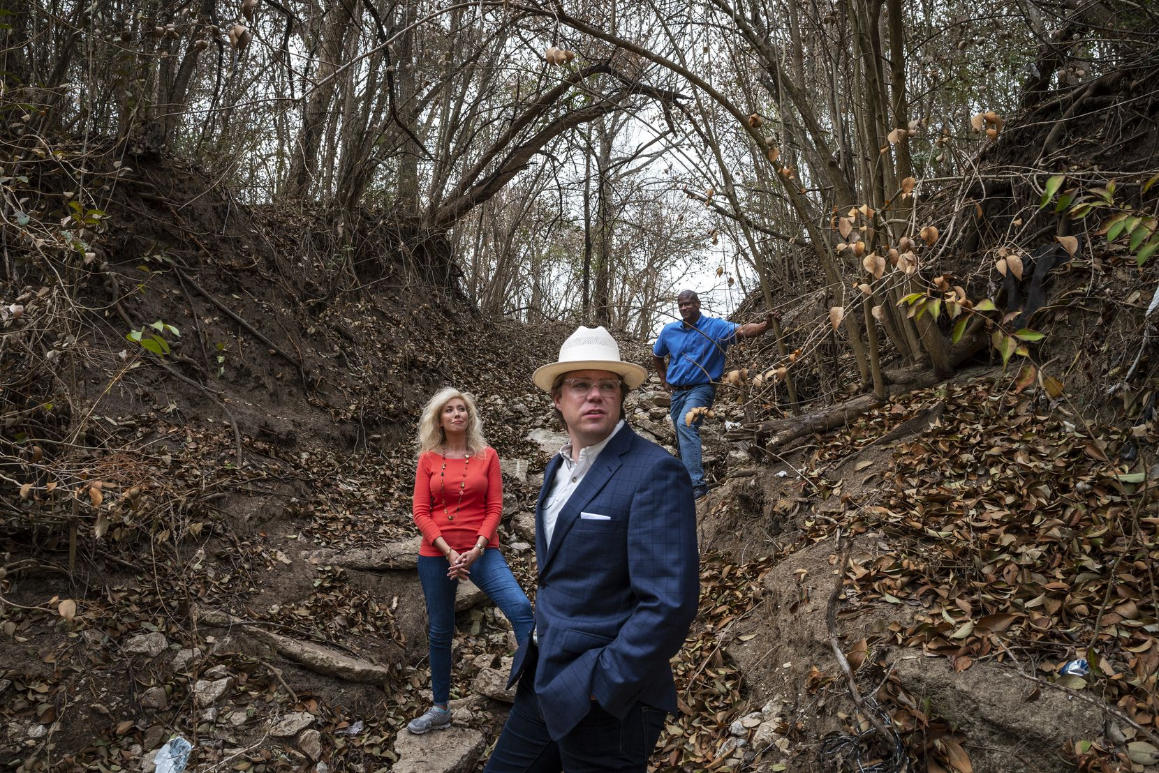 Robert Kent (front), Texas state director for the Trust for Public Land; Dallas Park Board president Calvert Collins Bratton; and John Jenkins, Dallas Park and Recreation director, stand near the bottom of a hill on the new parkland that leads to Woody Branch Creek.