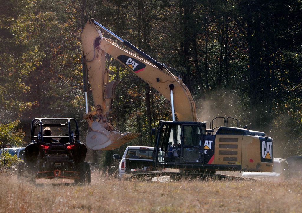 """Investigators with the Spartanburg County Sheriff's Office and Spartanburg Coroner's Office work the crime scene on property owned by Todd Kohlhepp, Friday, Nov. 4, 2016, in Woodruff, S.C., where a missing woman was found chained up in a large storage container. An body was found on the property as authorities were """"trying to make sure that we don't have a serial killer on our hands,"""" the sheriff said. Investigators were told the property could hold as many as three other corpses. (Tim Kimzey/The Spartanburg Herald-Journal via AP)"""