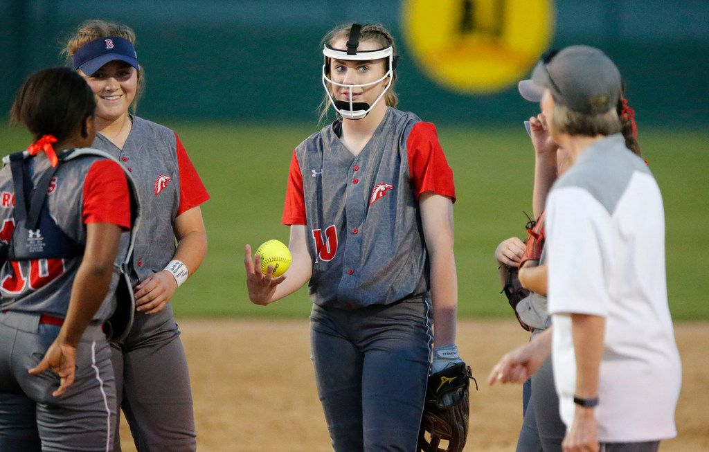 McKinney Boyd High School pitcher Kinsey Kackley (10) has a meeting on the mound with her coach during the second inning as McKinney High School hosted McKinney Boyd High School in a district 9-6A softball game at McKinney High School on Tuesday, March 26, 2019.  (Stewart F. House/Special Contributor)
