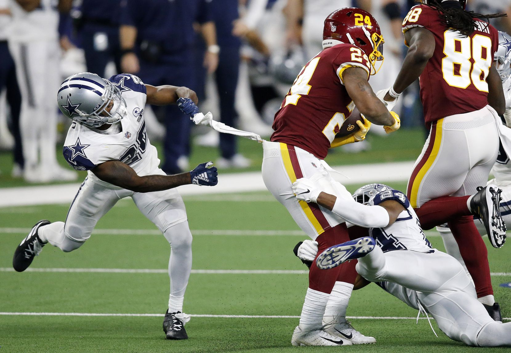 Dallas Cowboys cornerback Jourdan Lewis (26, left) and cornerback Chidobe Awuzie (24) try to bring down Washington Football Team running back Antonio Gibson (24) during the third quarter at AT&T Stadium in Arlington, Thursday, November 26, 2020. (Tom Fox/The Dallas Morning News)