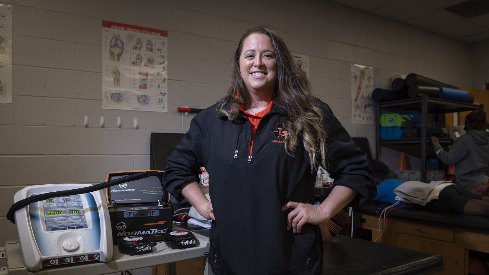 Jordan Hart, head athletic trainer for Lancaster High School, stands next to an ultra sound and electric stimulation device used on muscles, inside the school's athletic training room in Dallas, on Tuesday, March 09, 2021.