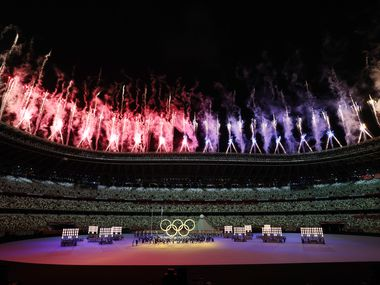 Fireworks go off as the Olympic rings are shown during the opening ceremony for the postponed 2020 Tokyo Olympics at Olympic Stadium on Friday, July 23, 2021, in Tokyo, Japan.