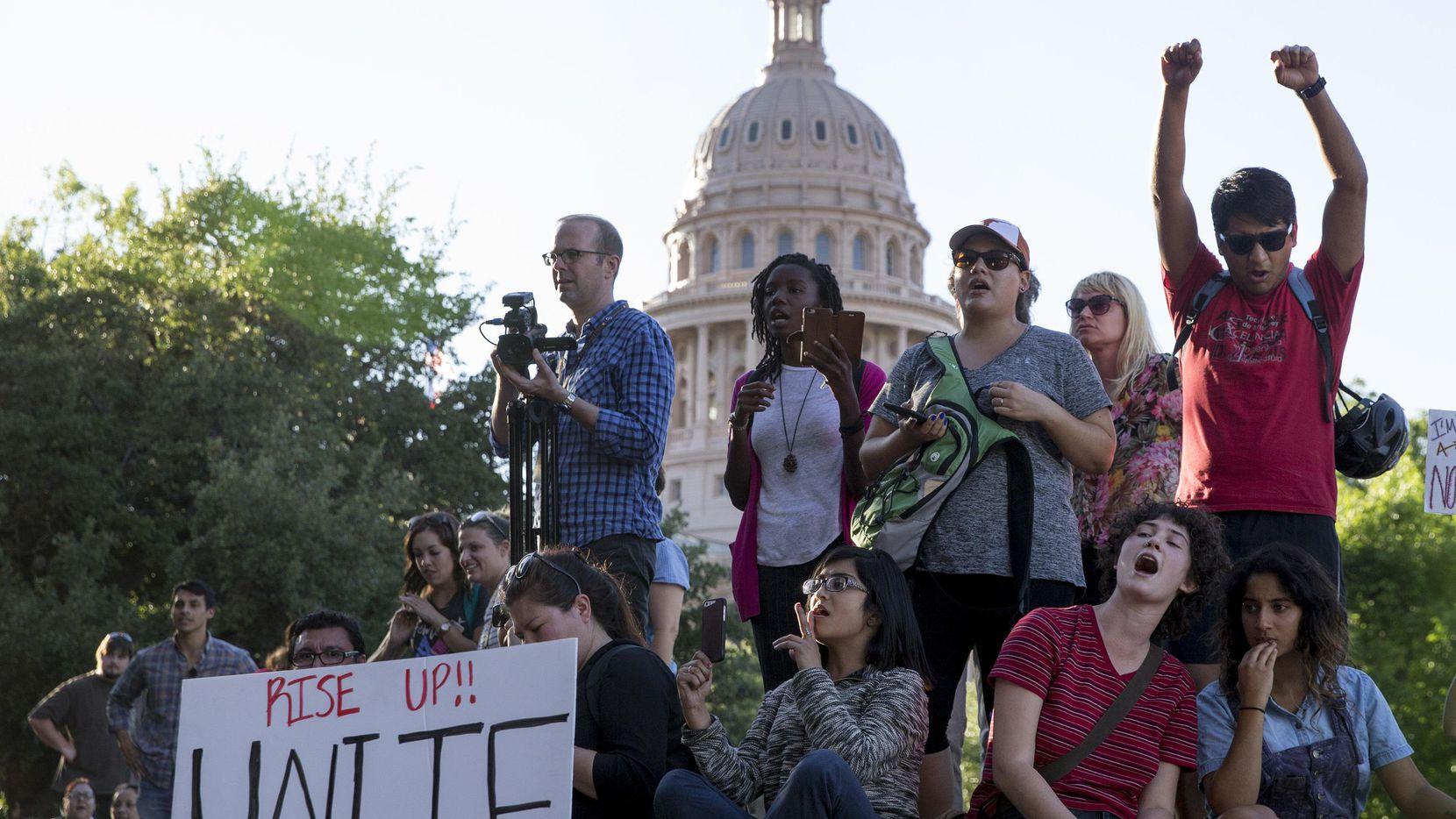 Unos manifestantes que están contra la medida SB4, se manifiestan afuera del edificio de Departamento de Seguros de Texas, donde el gobernador republicano, Greg Abbott, tiene su oficina en Austin, Texas. (AP/JAY JANNER)
