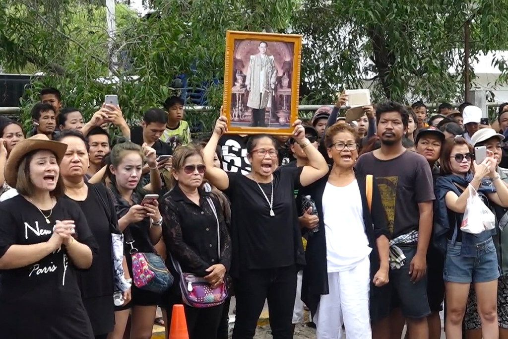 In this image made from video taken on Sunday, Oct. 16, 2016, a woman holds a portrait of Thailand's King Bhumibol Adulyadej as they publicly shame Umaporn Sarasat as she arrives at a police station to face charges of insulting the monarchy in Koh Samui, Thailand. A Thai woman accused of insulting the country's late king was forced to kneel before his portrait outside a police station on the tourist island of Samui as several hundred people bayed for an apology.