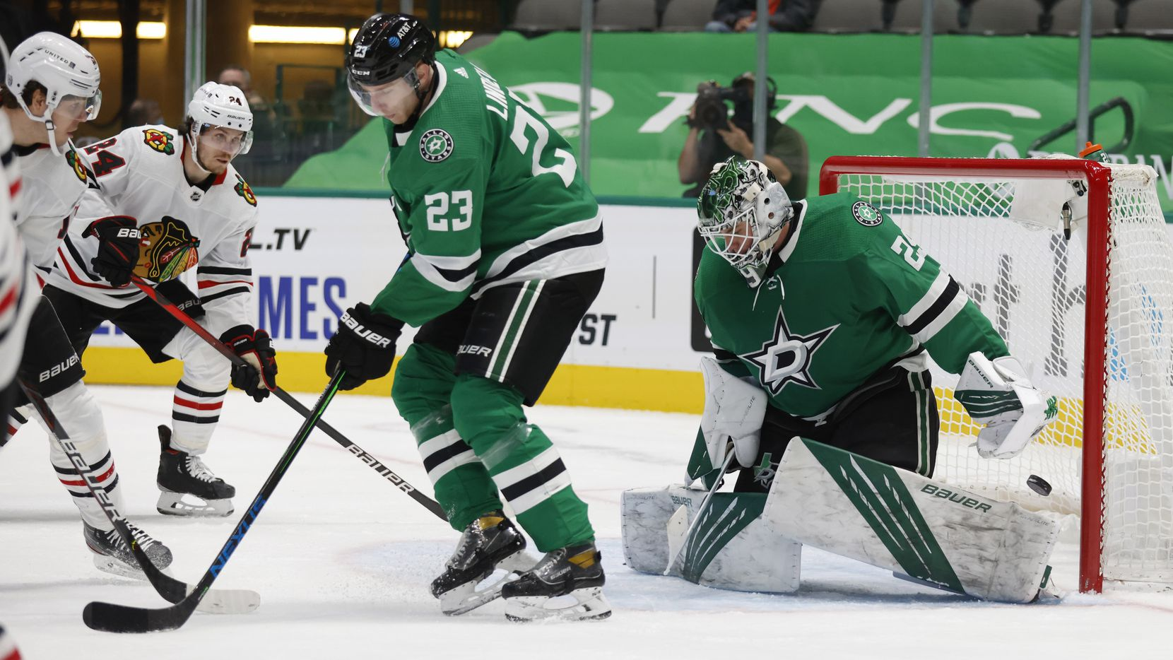 Chicago Blackhawks center Mattias Janmark (13) watches as he scores a goal on Dallas Stars goaltender Jake Oettinger (29) in front of Dallas Stars defenseman Esa Lindell (23) during the second period of play at American Airlines Center on Tuesday, February 9, 2021 in Dallas.