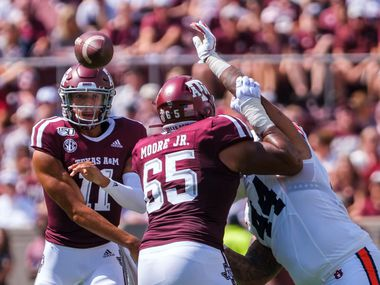Texas A&M quarterback Kellen Mond (11) gets a block from offensive lineman Dan Moore Jr. (65) on Auburn defensive tackle DaQuan Newkirk (44) as he gets off a pass during the first quarter of an NCAA football game at Kyle Field on Saturday, Sept. 21, 2019, in College Station, Texas.