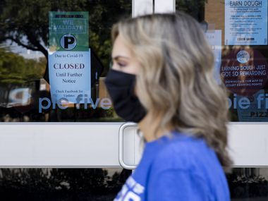 Graduate student Maddie Eby passes by a restaurant on the University of Texas at Arlington campus that is closed because of COVID-19.