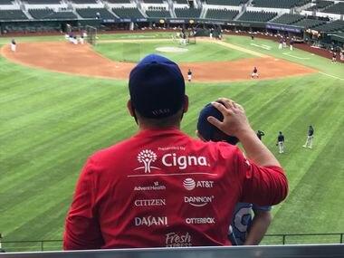 George Richards toca la cabeza de su hijo, George Richards III, antes del inicio del partido entre los Rangers de Texas y Brewers de Milwaukee en el Globe Life Field de Arlington, el 29 de marzo de 2021.