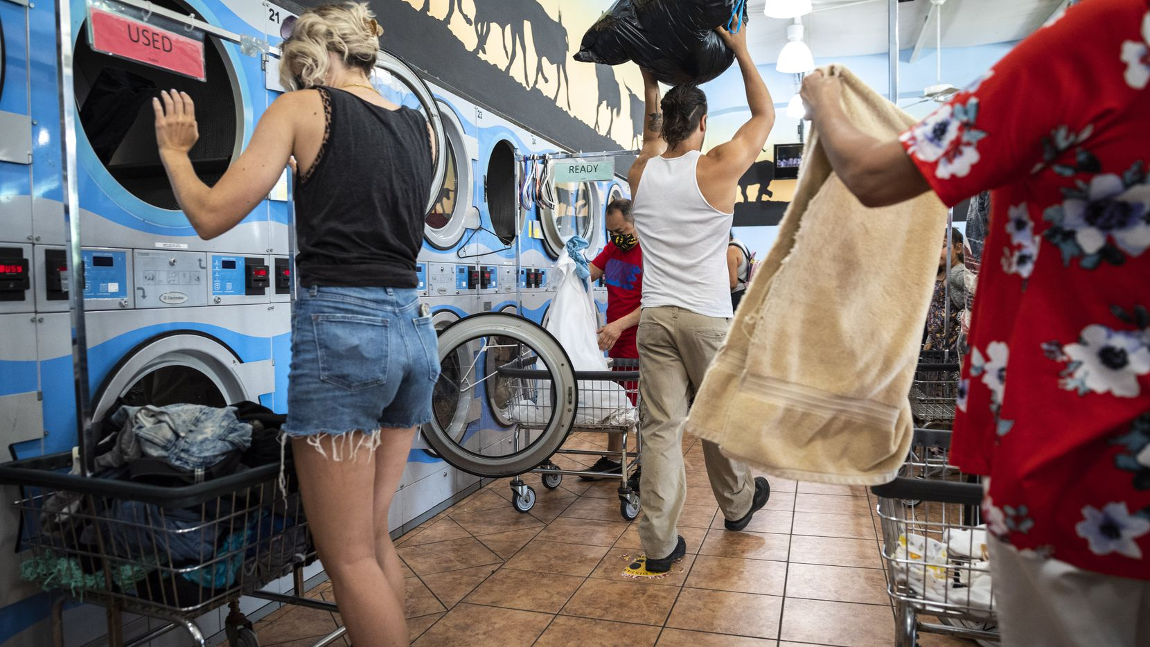 Volunteer Julian Shaffer, center, carries a load of dried clothes after washing for inventory as members of the organization Say It With Your Chest, washed clothes for homeless people, at Xpress Wash N Dry in Dallas, on July 25, 2021.