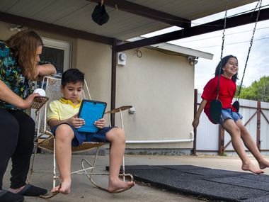 Maria Tobias (left) helps her 8-year-old son, Javier Garcia (center), during a reading exercise as his twin sister Viviann swings nearby at their home in Dallas. The twins both have autism, speech delays and other learning disabilities. Tobias is frustrated that she hasn't been provided with adequate resources to educate her children at home during the COVID-19 pandemic.