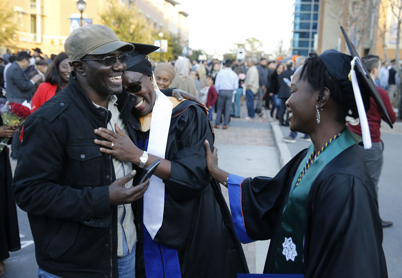 Cheikh Sy hugs his wife Ndeye Ndaw as they share a laugh with their daughter Awa Sy outside College Park Center at the University of Texas at Arlington shortly after graduation ceremonies. Ndeye earned a master's degree and her daughter Awa earned her bachelor's degree.